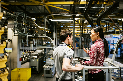Image of two people in factory discussing work